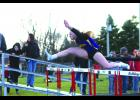 Left: Megan Groe clears the hurdle as the anchor for the girls shuttle hurdle team at the Hampton CoEd meet last Friday.